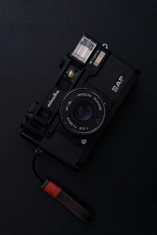 black Minolta AF point-and-shoot camera on black surface