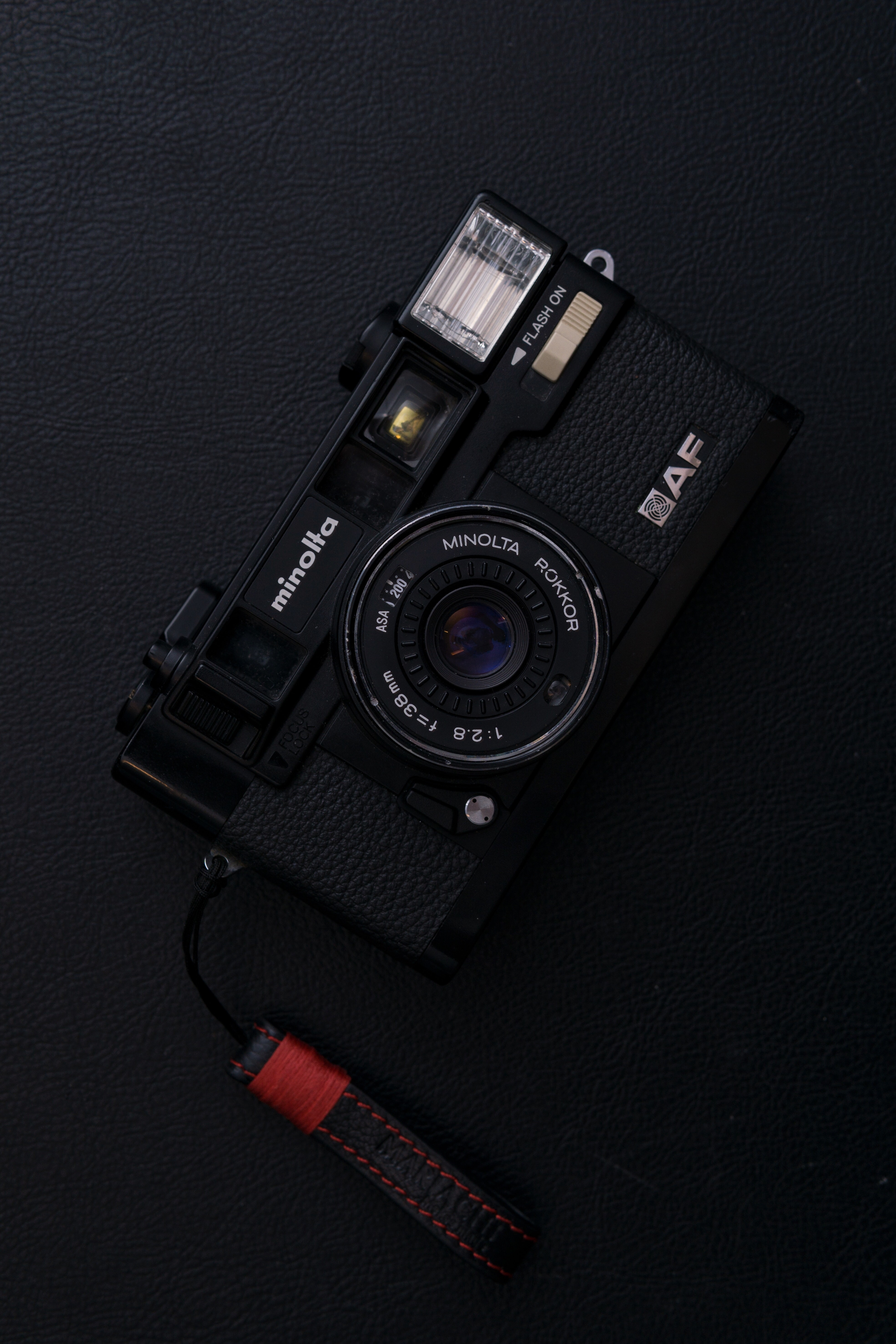 black Minolta AF point-and-shoot camera on black surface