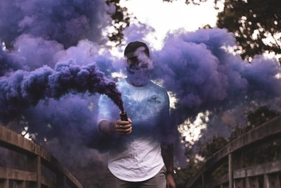 man holding purple smoke smoke grenade teams background