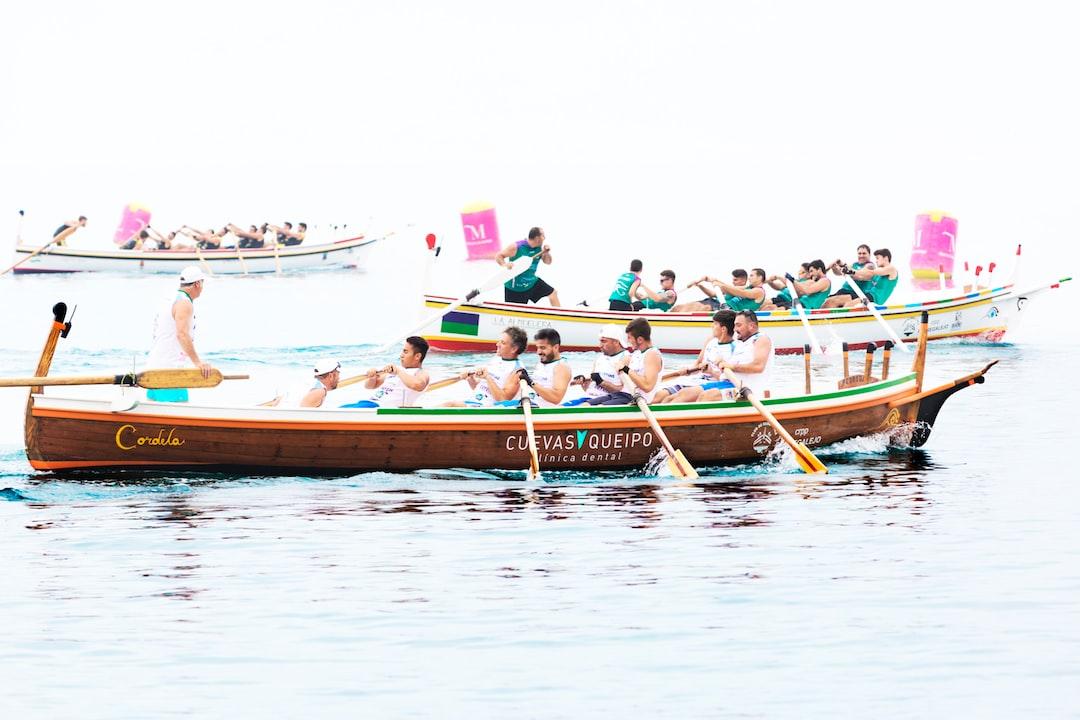En primer término el equipo junior de Remo y Pala Tradicional Torremolinos, La Carihuela compitiendo en la regata de barcas de jábega celebrada en las Playas de El Palo (Málaga) realizando un último esfuerzo para alcanzar la meta.