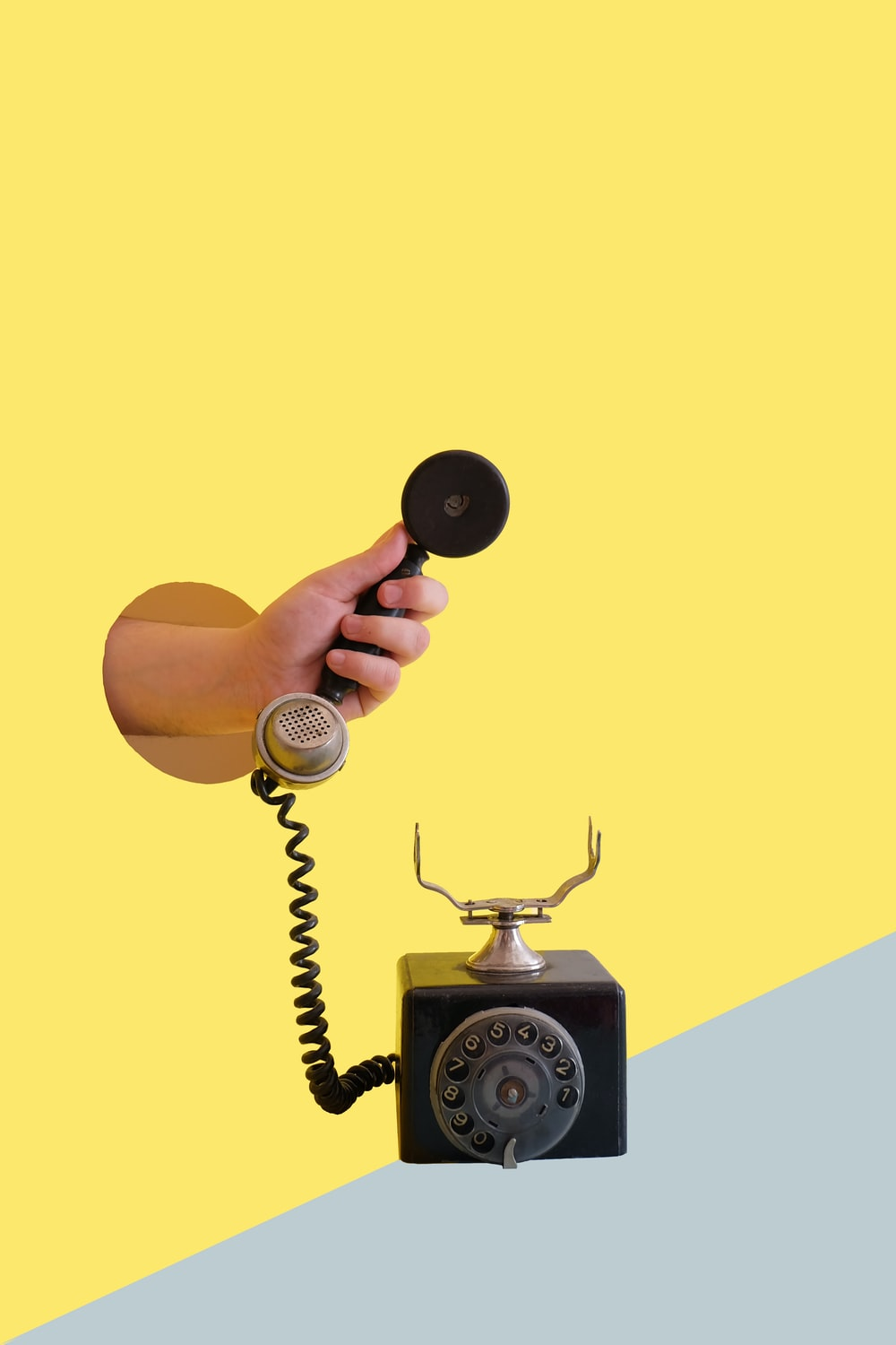 person holding black rotary telephone