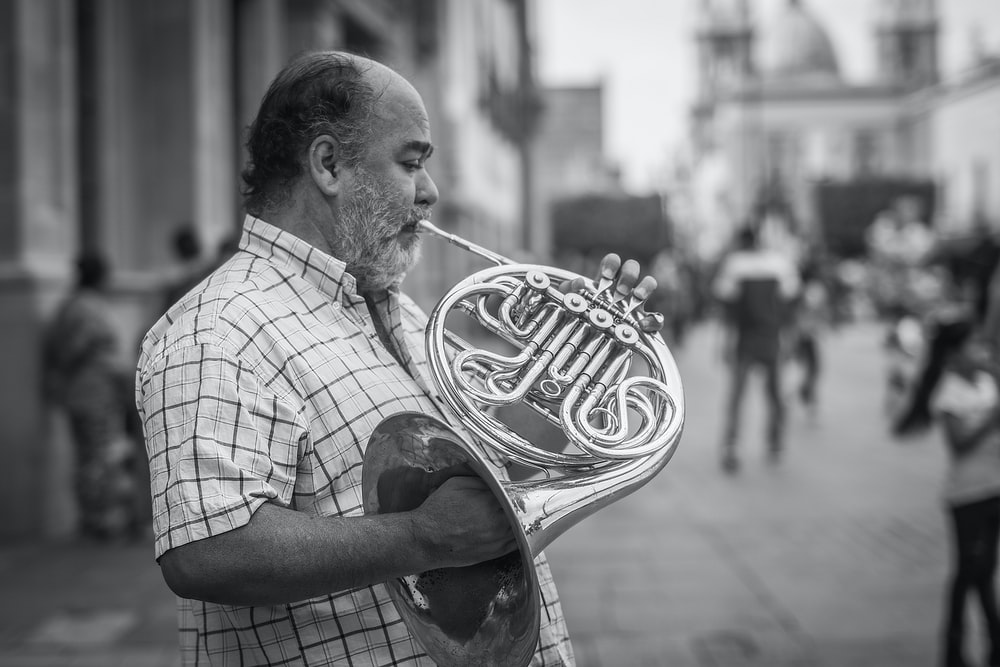 grayscale photography of man playing French horn