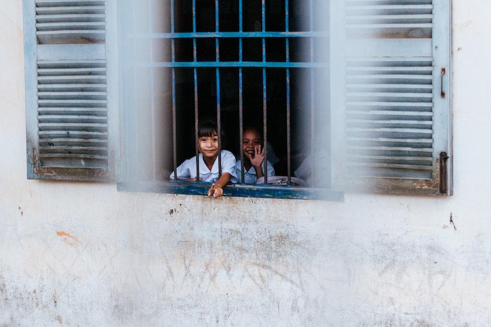 kids sitting near blue window grills