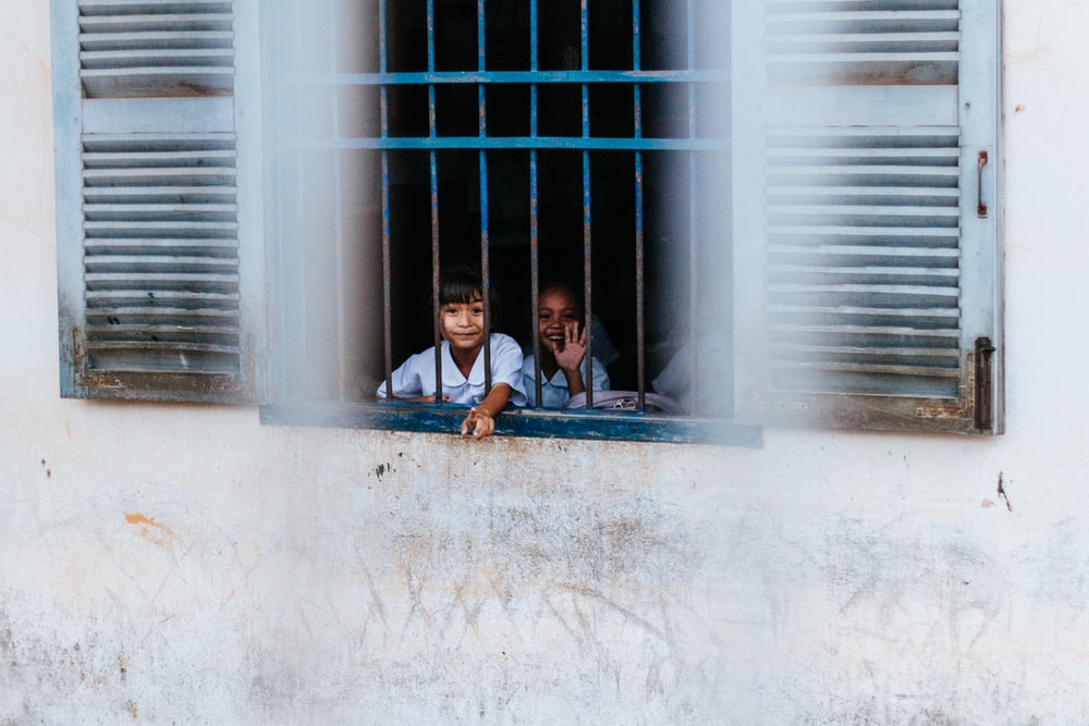 kids sitting near blue window grills