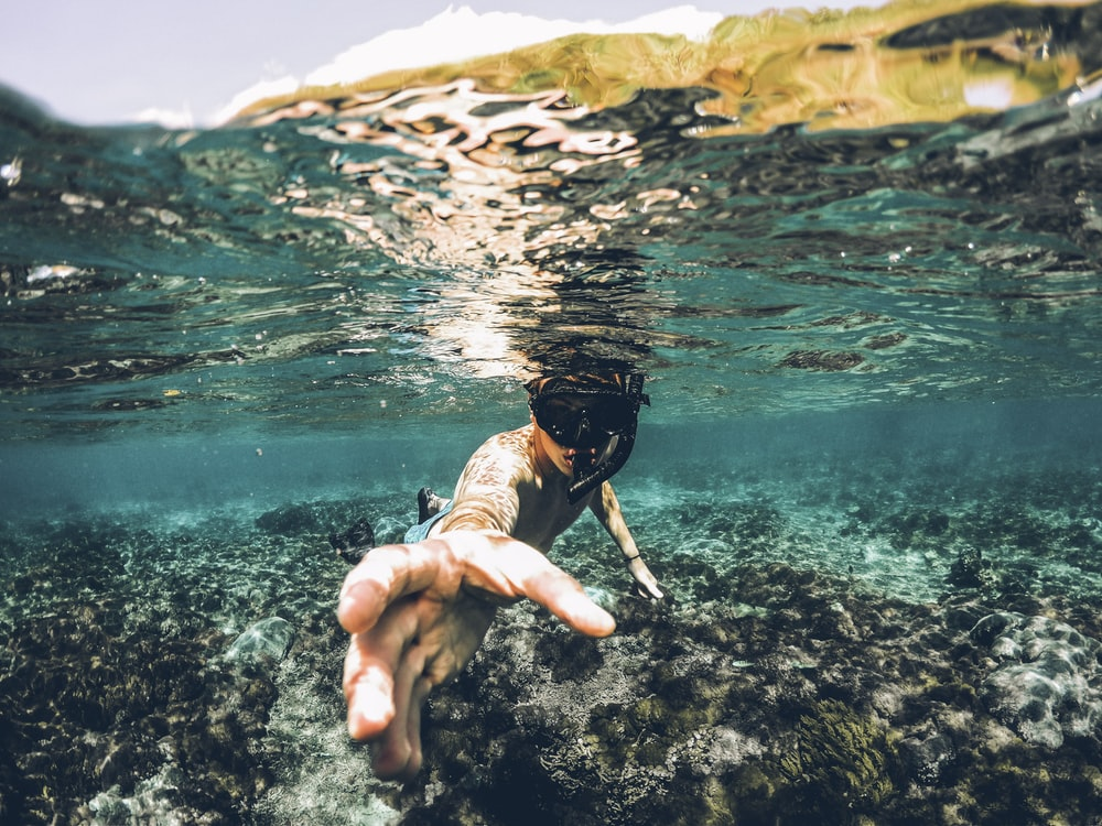 underwater photography of man wearing snorkel lending his hand