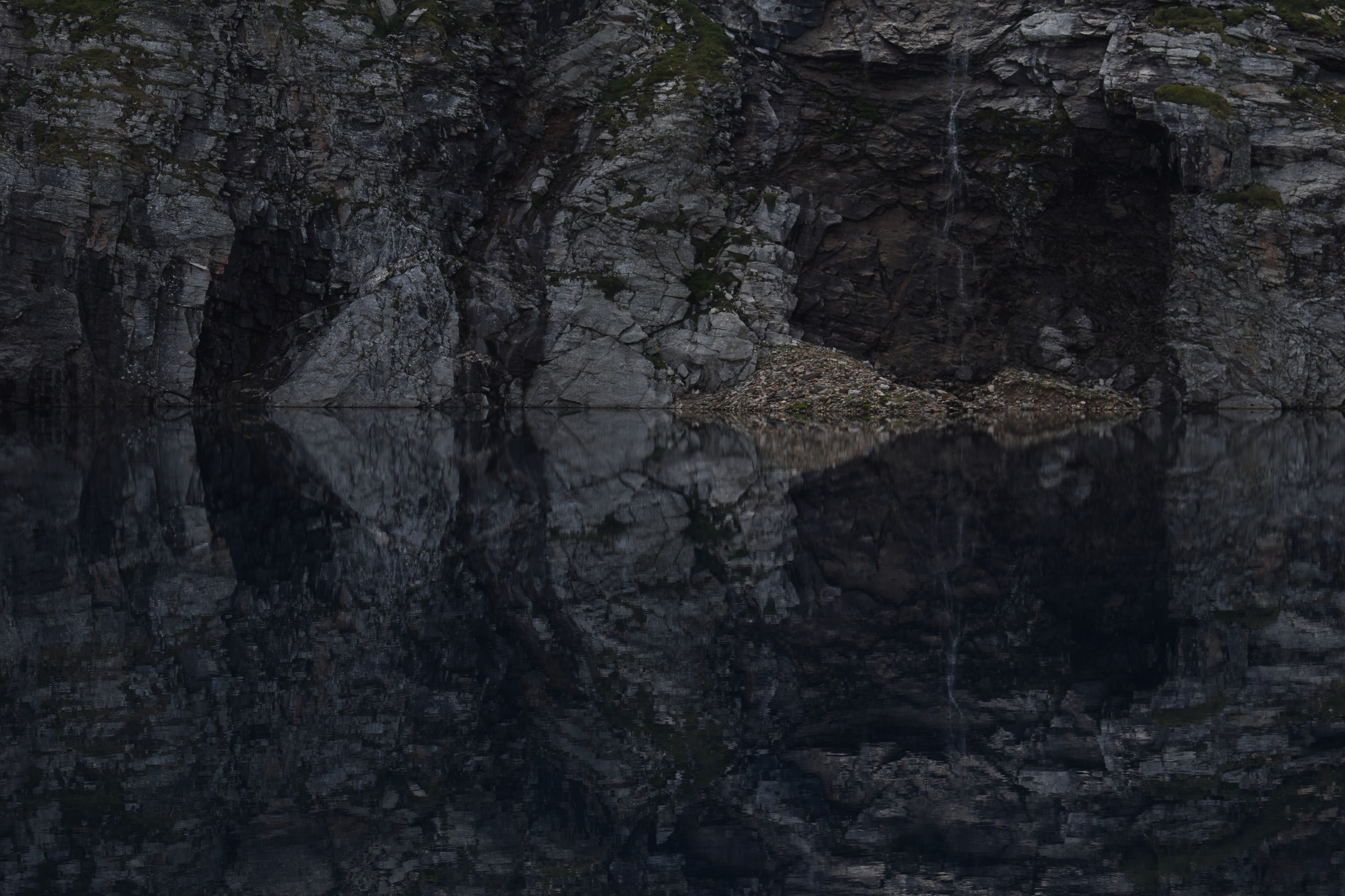 brown and gray cave with body of water