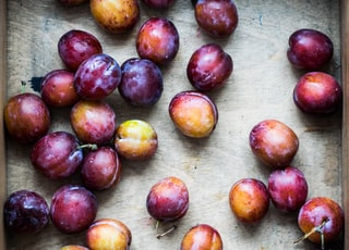 bunch of Spanish plum on brown surface