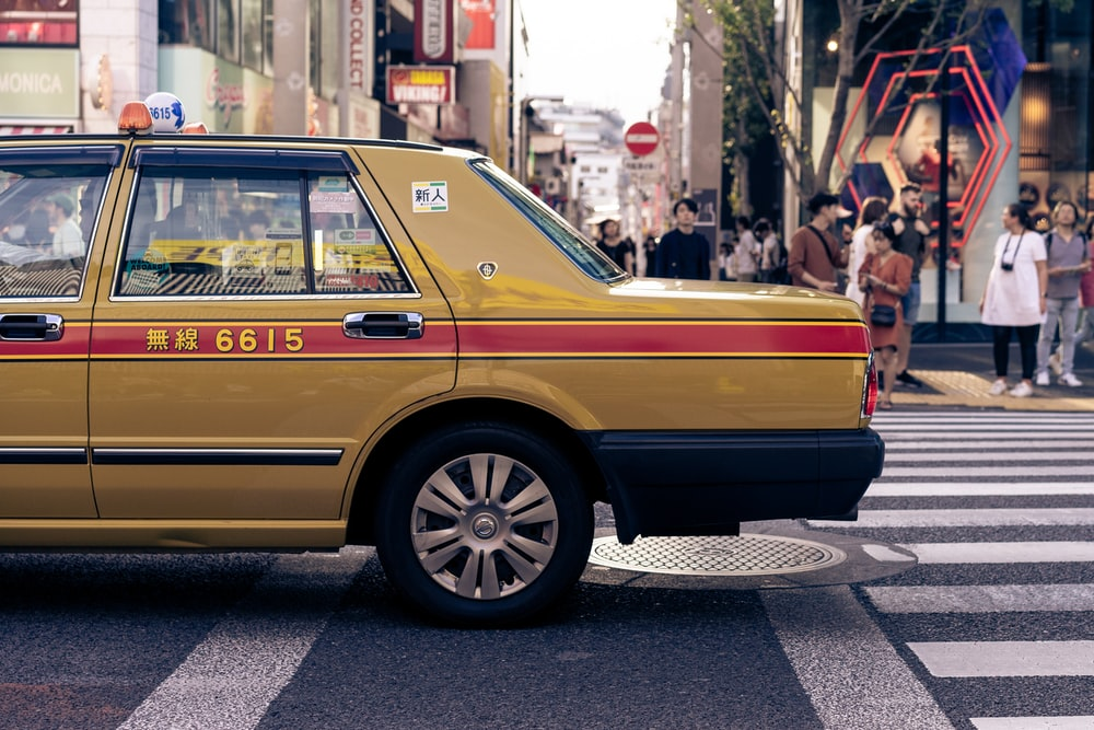 yellow and red 6615 taxi on road during daytime