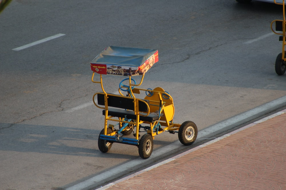 yellow pedal cart on road