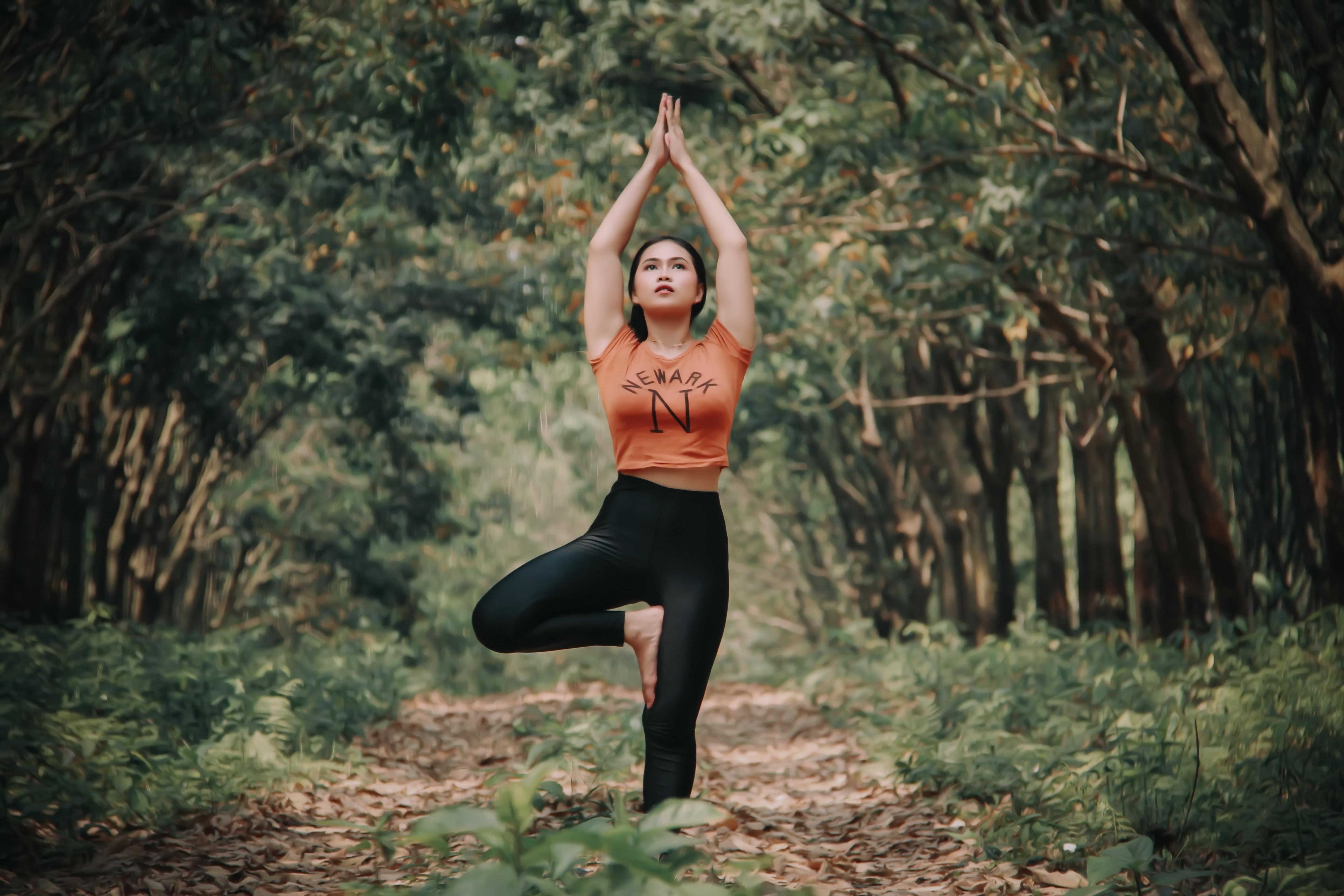 woman doing yoga near trees