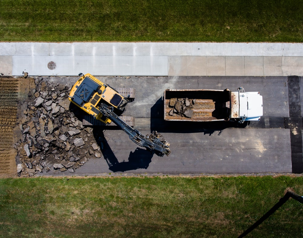 aerial photography of yellow heavy equipment beside white dump truck at daytime