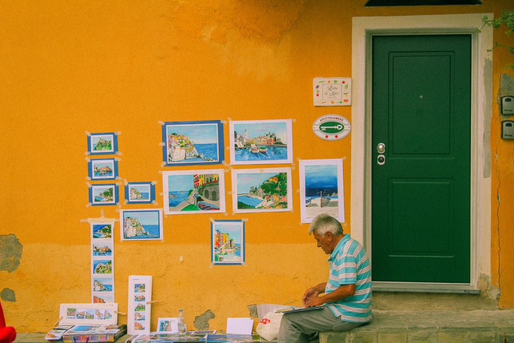 man near closed green window with paintings