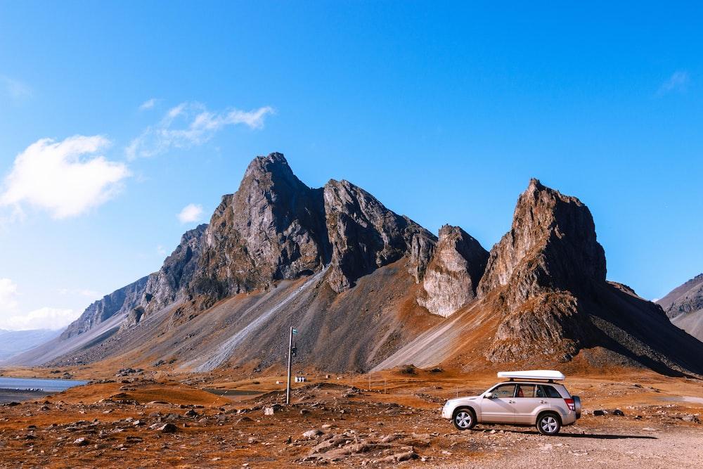 gray SUV parked near rock cliffs