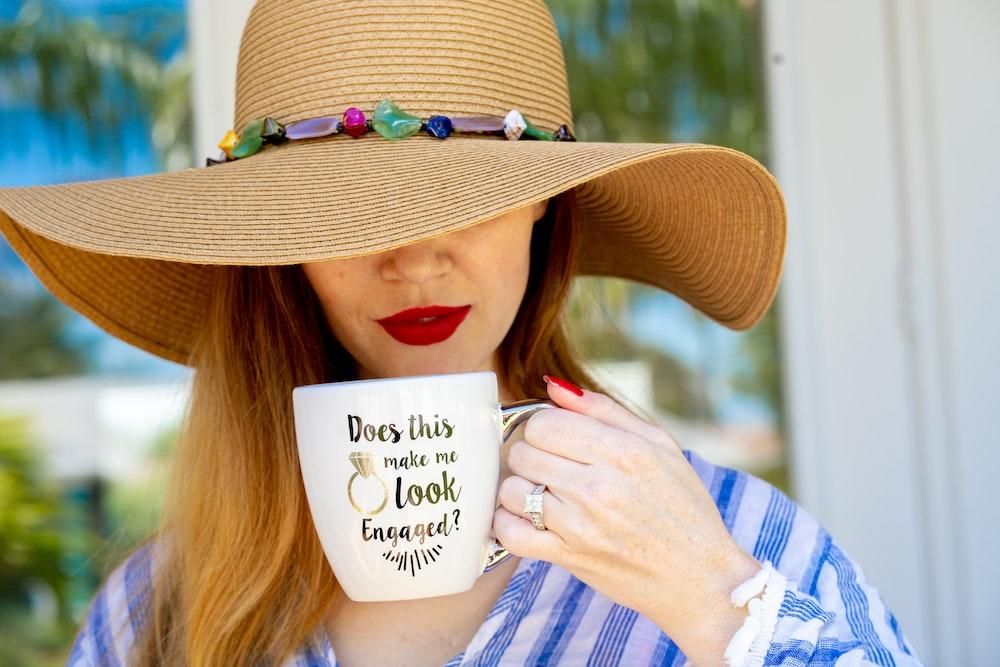 woman wearing brown hat holding white mug