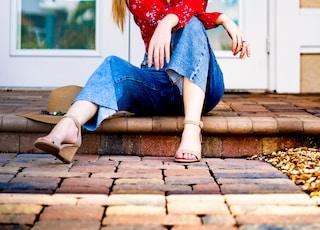 woman wearing blue jeans sitting on floor