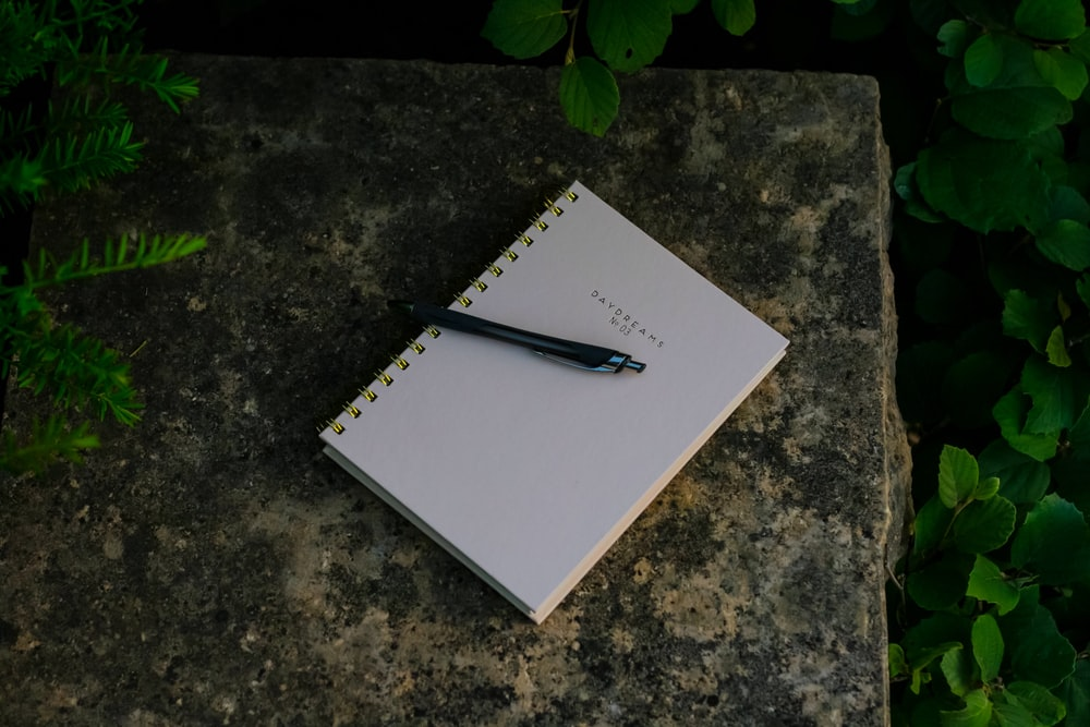 black click pen on notebook
