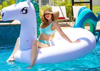 woman riding on white plastic unicorn buoy