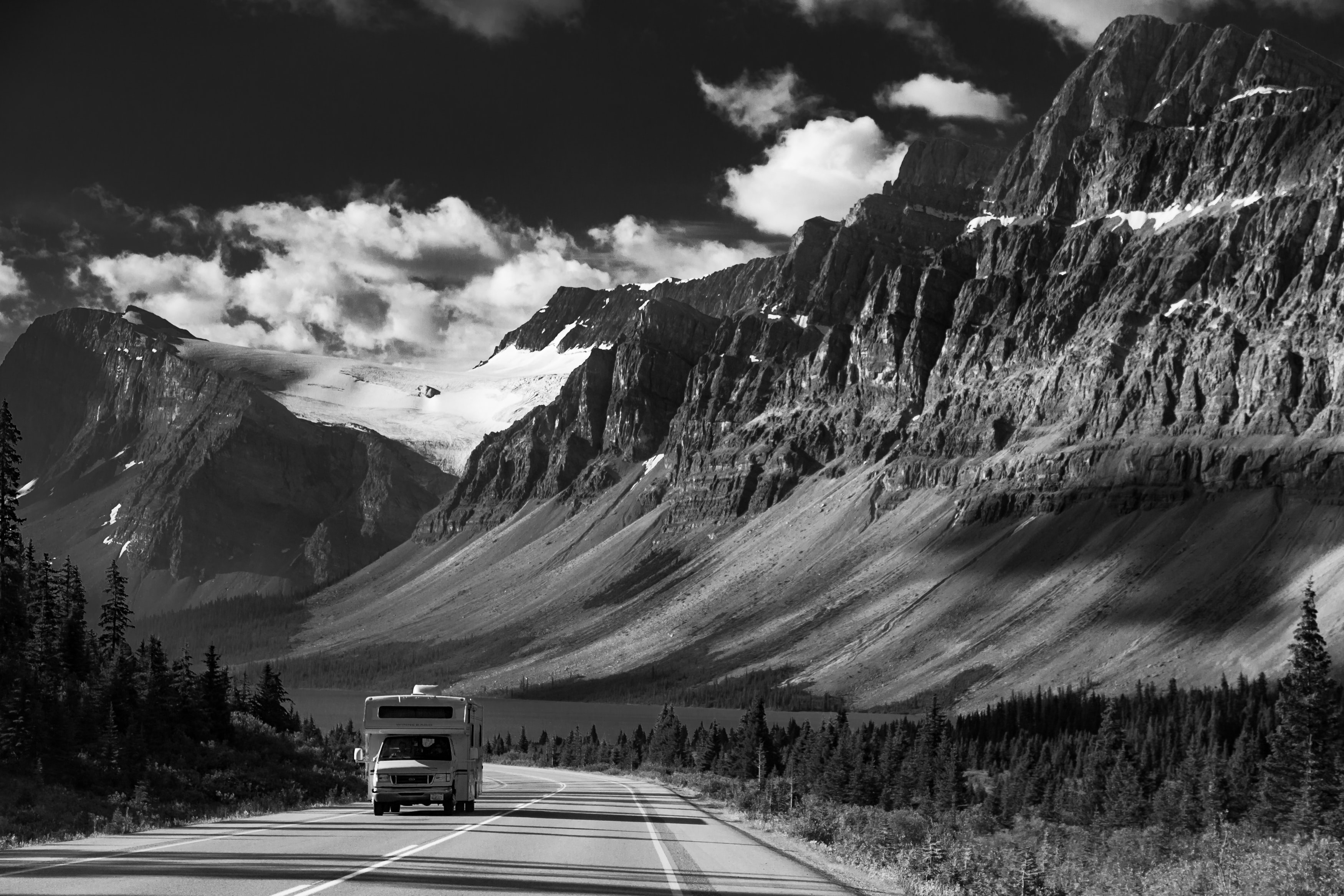 grayscale photo of vehicle passing on road near mountain range