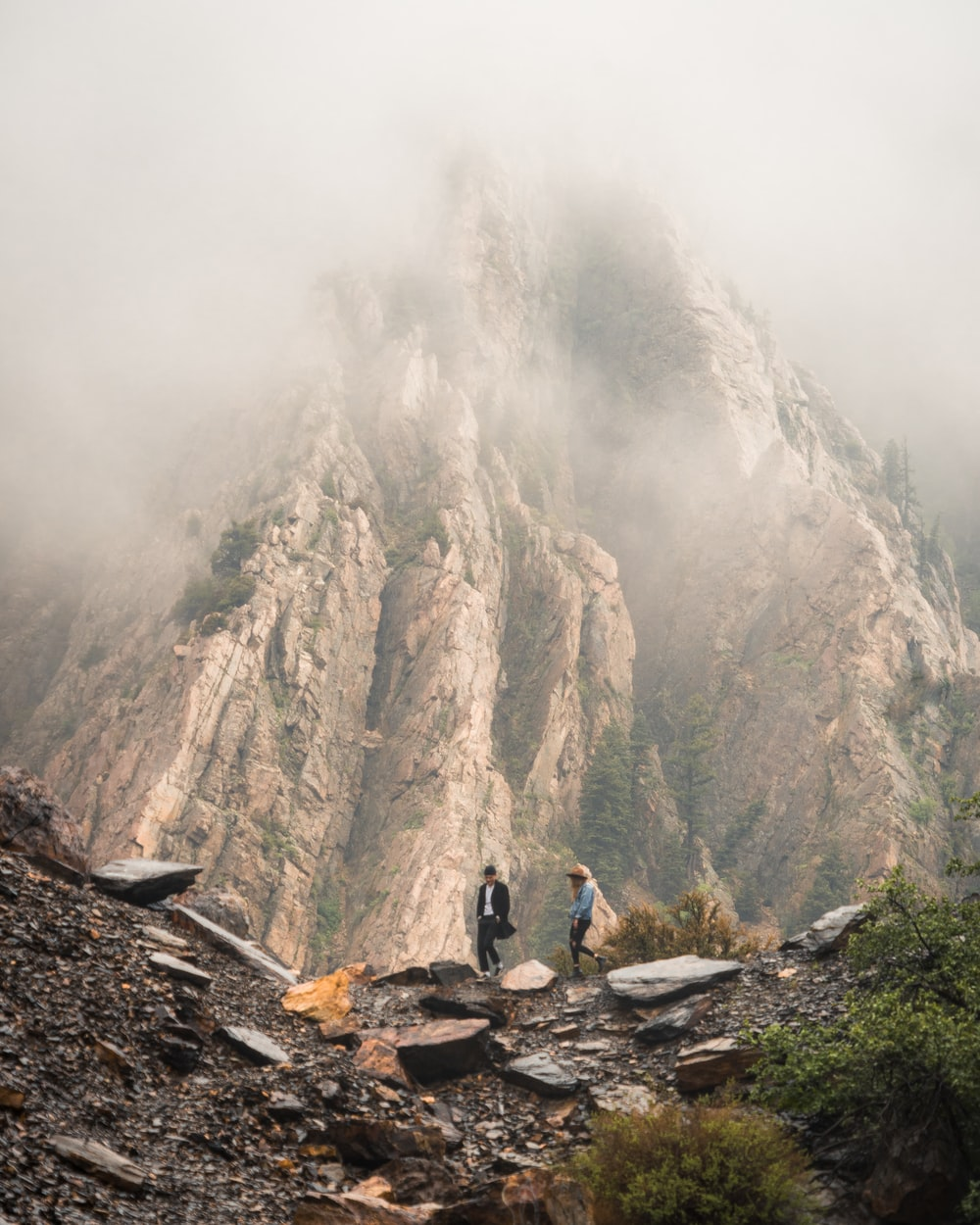 two person walking near rock formation