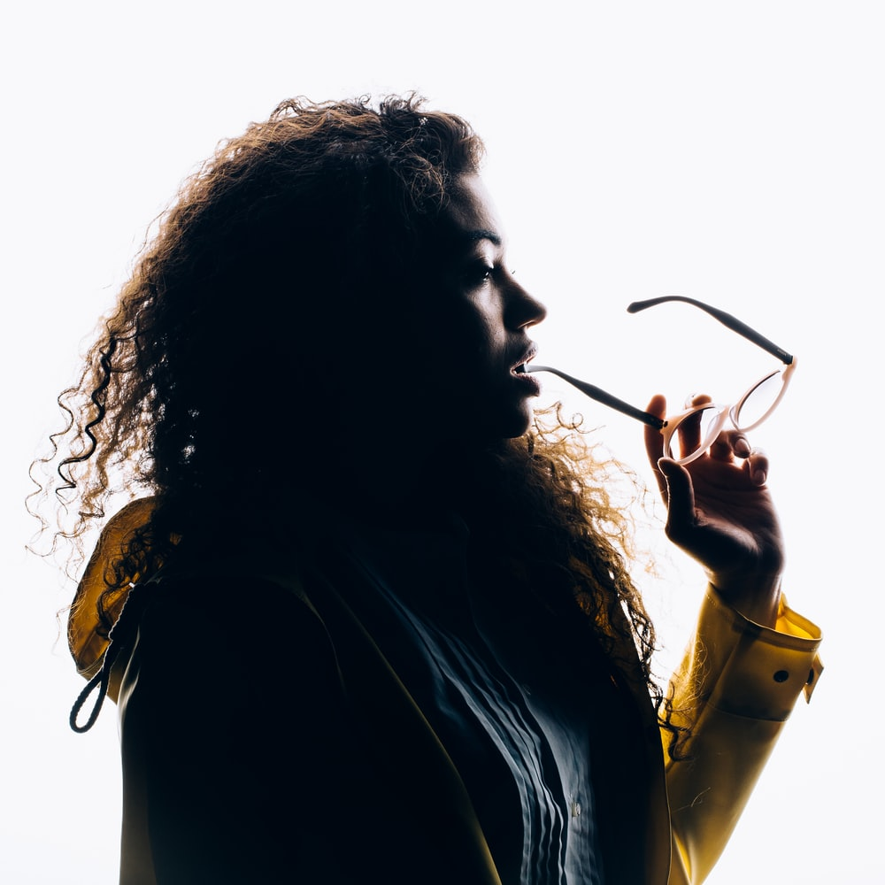 silhouette photo of woman biting her eyeglasses