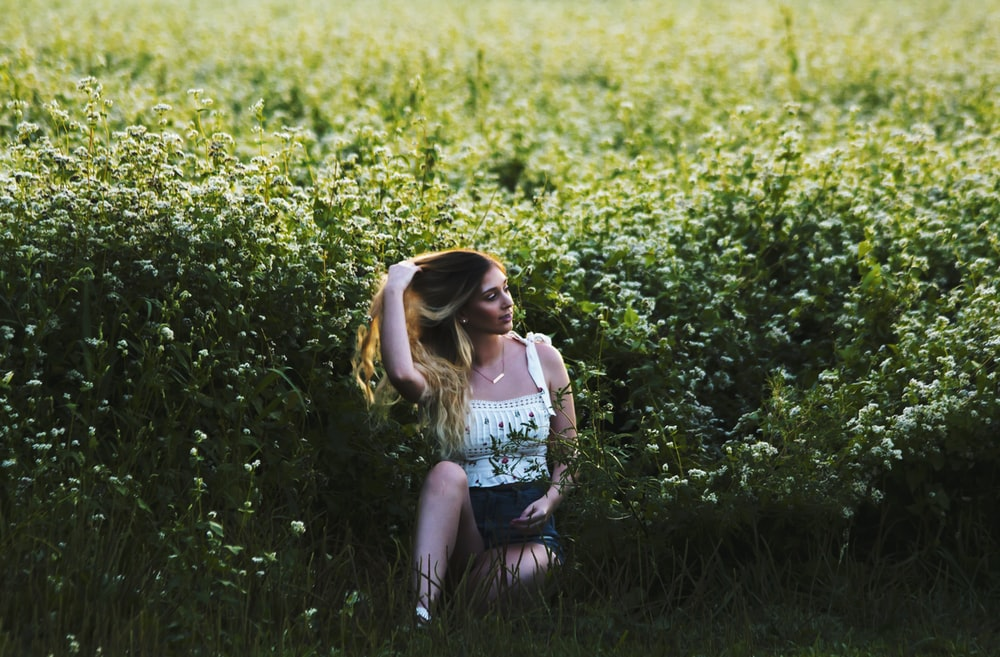 woman sitting at flower meadow