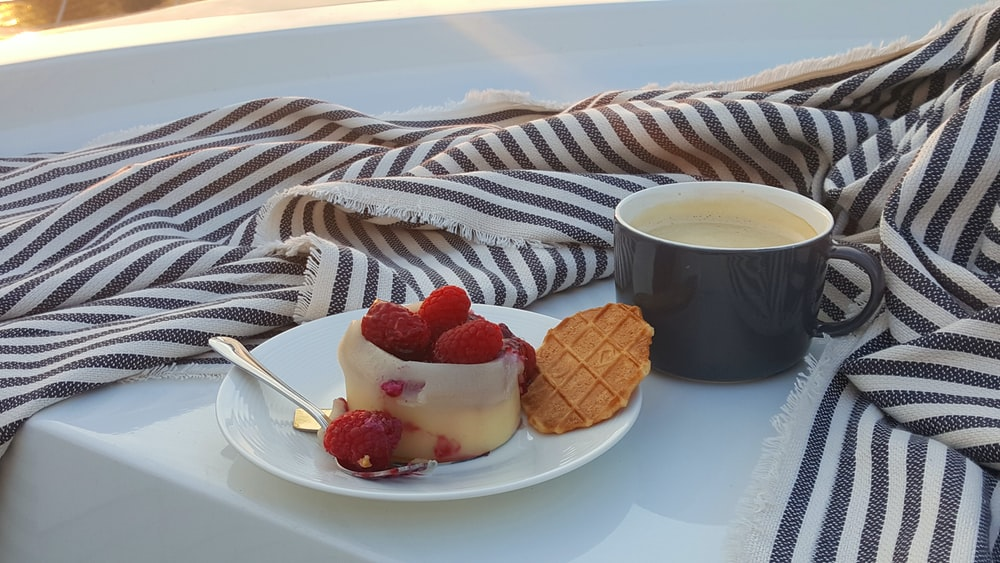 strawberries and black ceramic mug with coffee