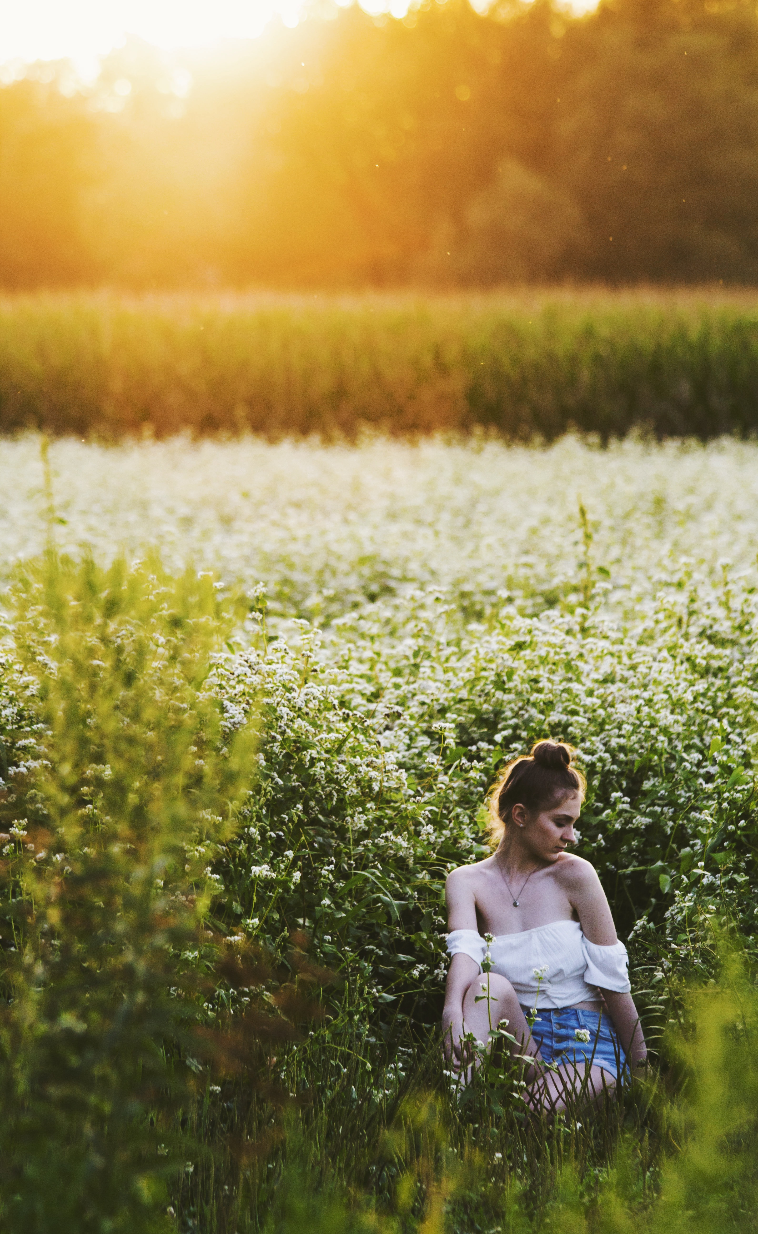 golden hour photography of woman in white top and blue denim shorts