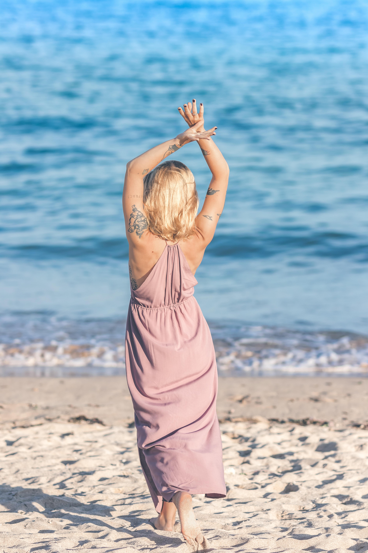 woman wearing pink dress raising both hands while walking on shore