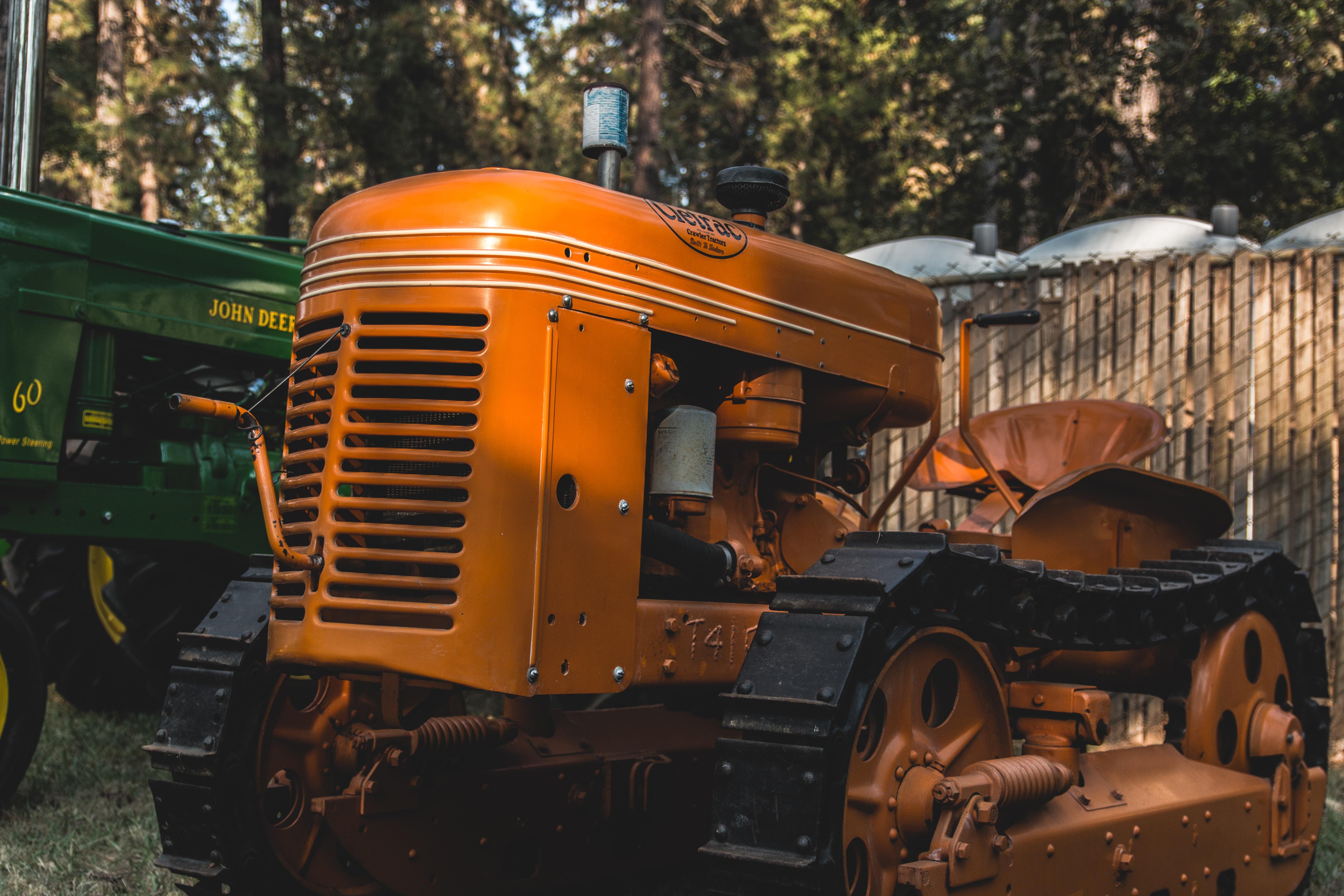 orange tractor beside John Deere tractor