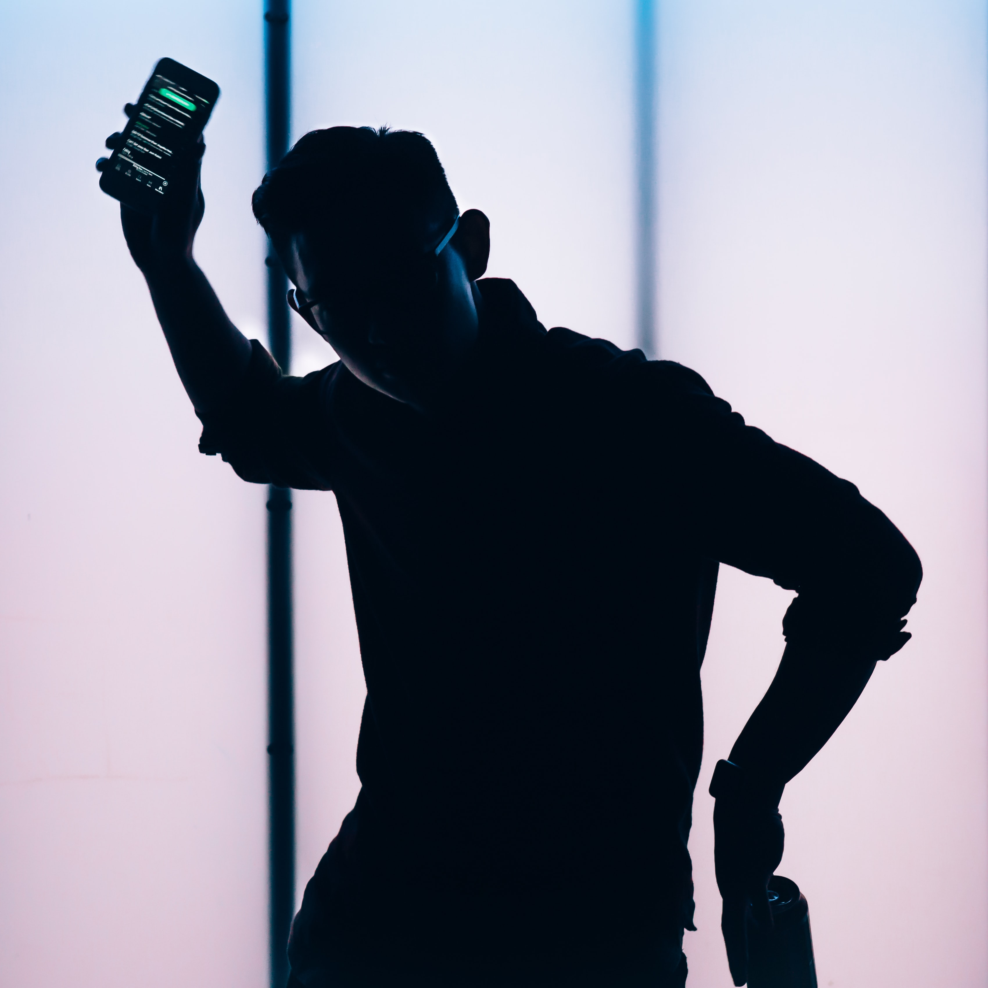 silhouette of man holding smartphone