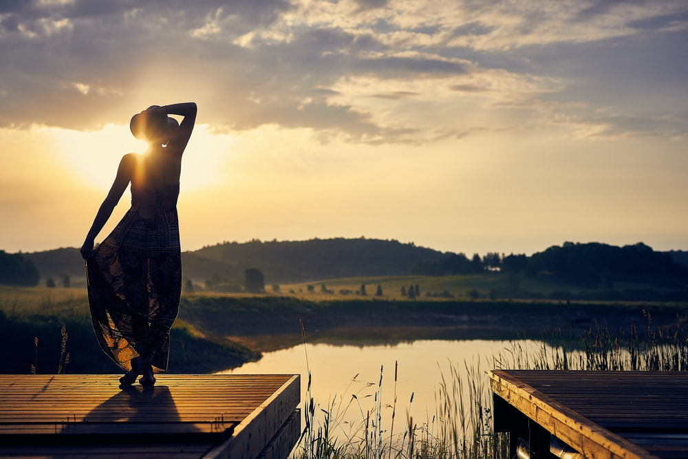 silhouette of woman standing on brown wooden dock during golden hour