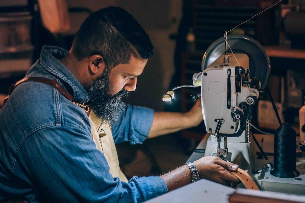 man sewing brown belt