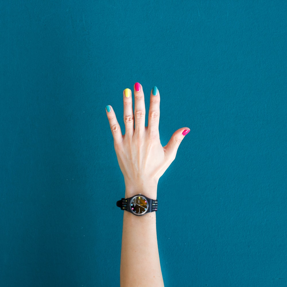 person wearing round black analog watch with black strap