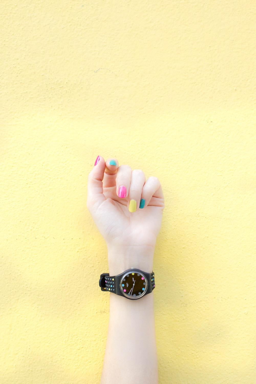 person wearing round black analog watch at 9:46