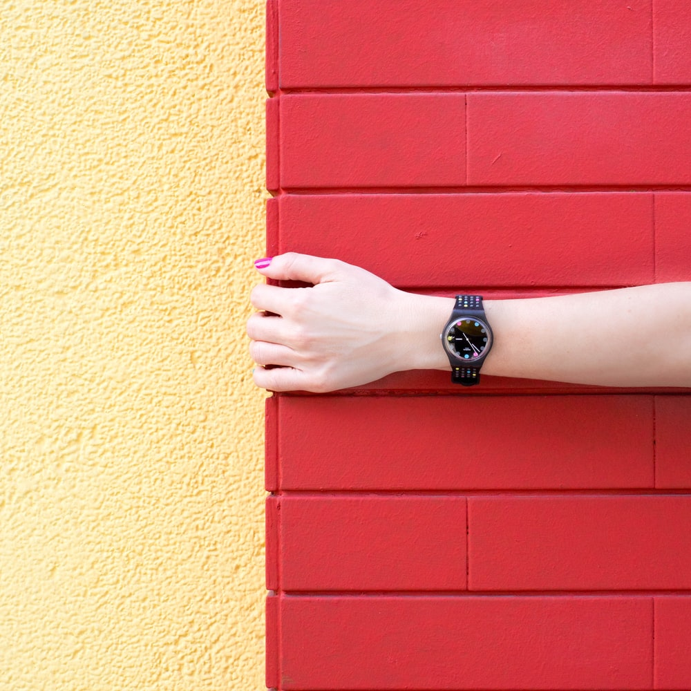 person wearing black analog watch holding red brick wall