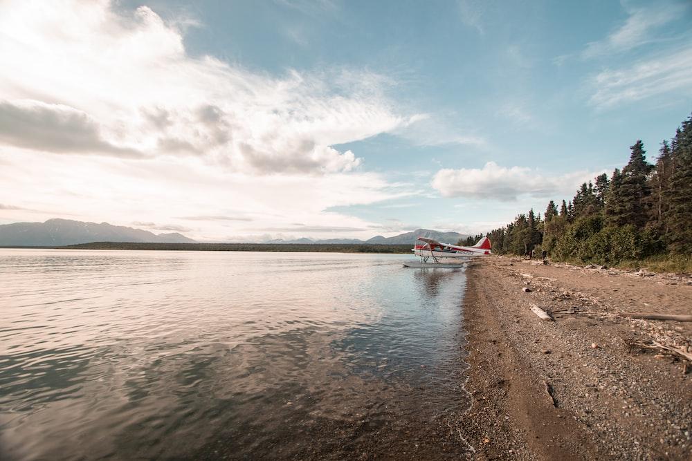 white bi-plane on water