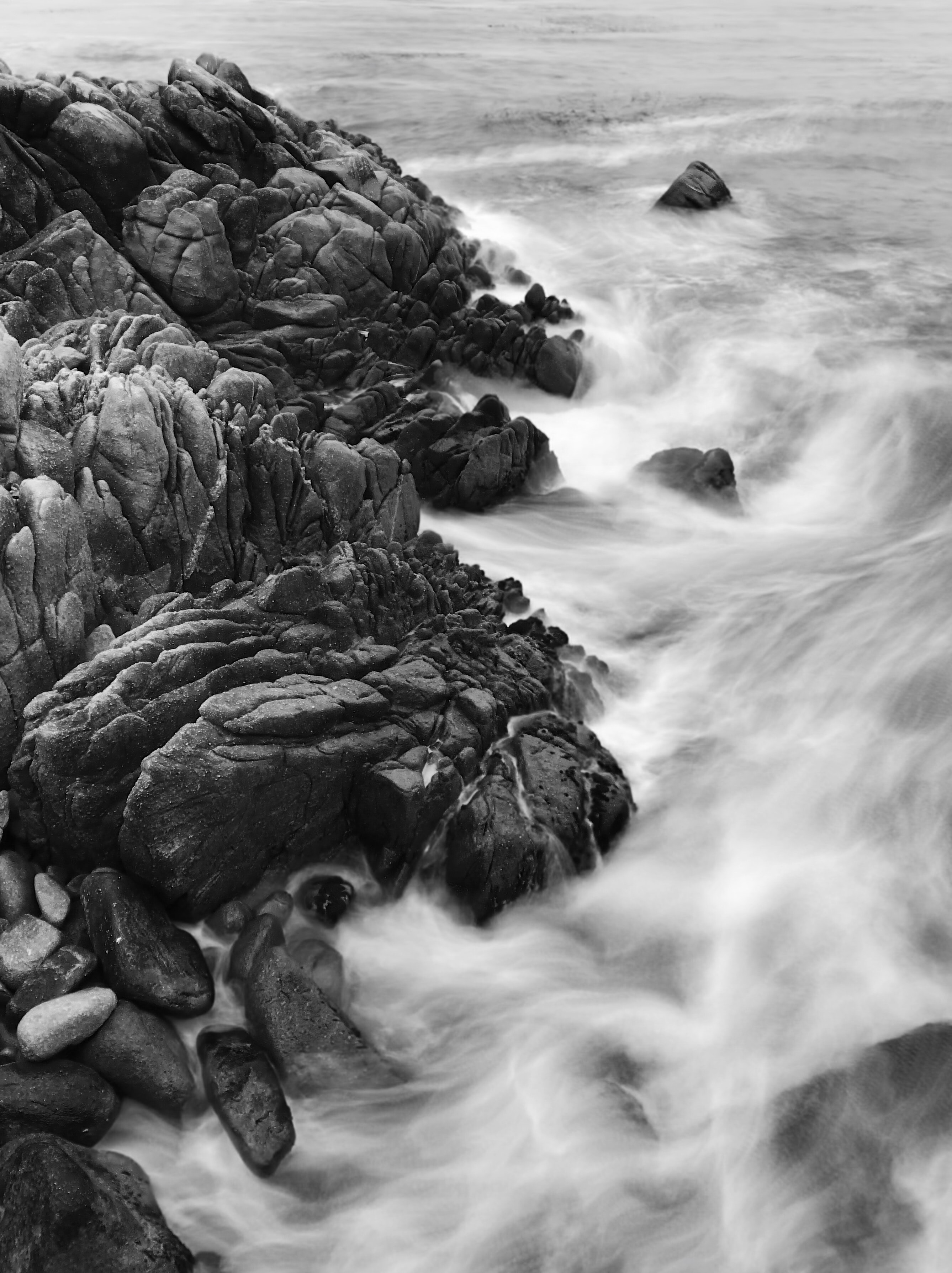 grayscale photography of cliff with ocean waves