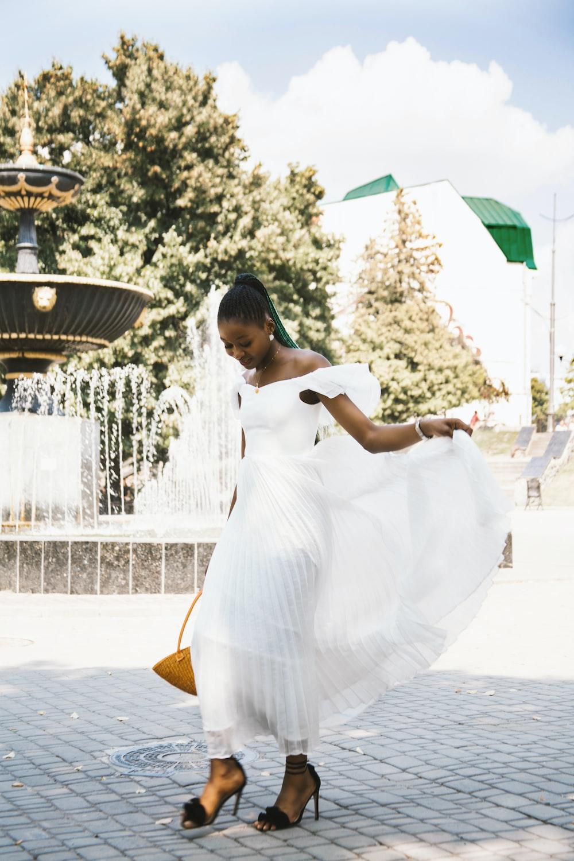 woman in white dress standing near fountain