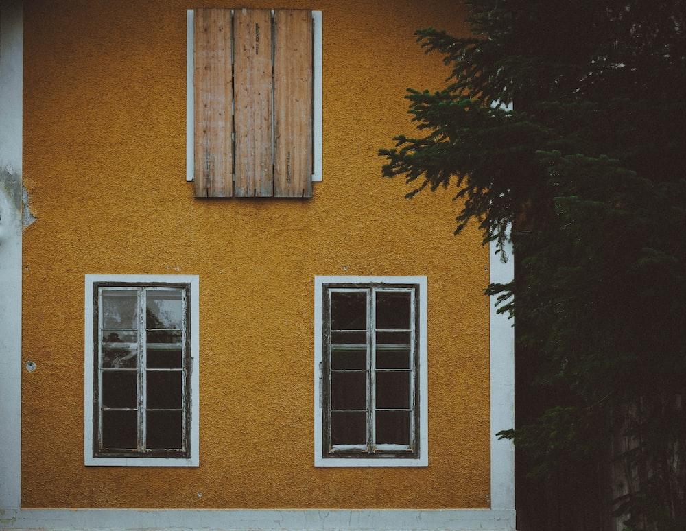 brown concrete house near green tree