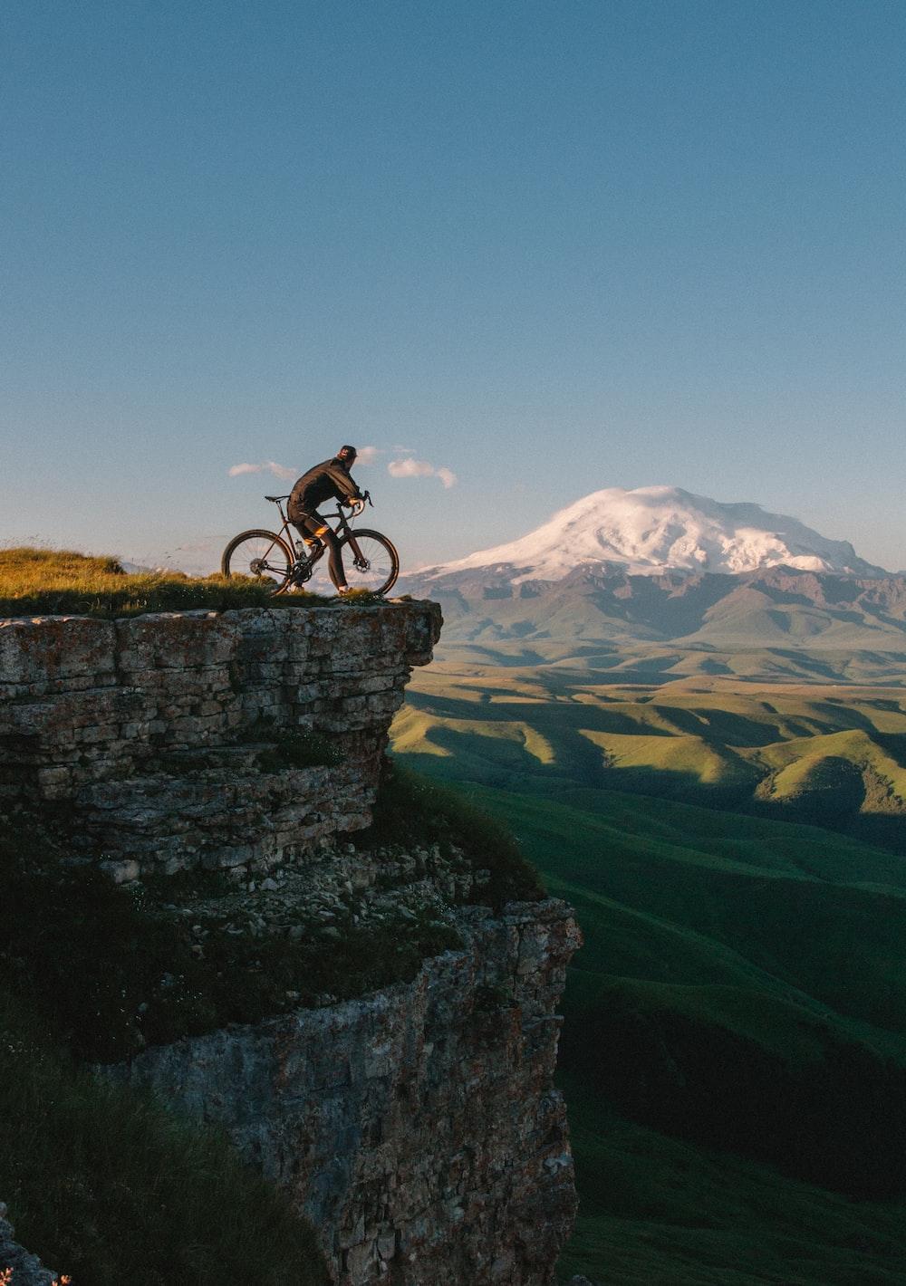 man riding bike on cliff at daytime