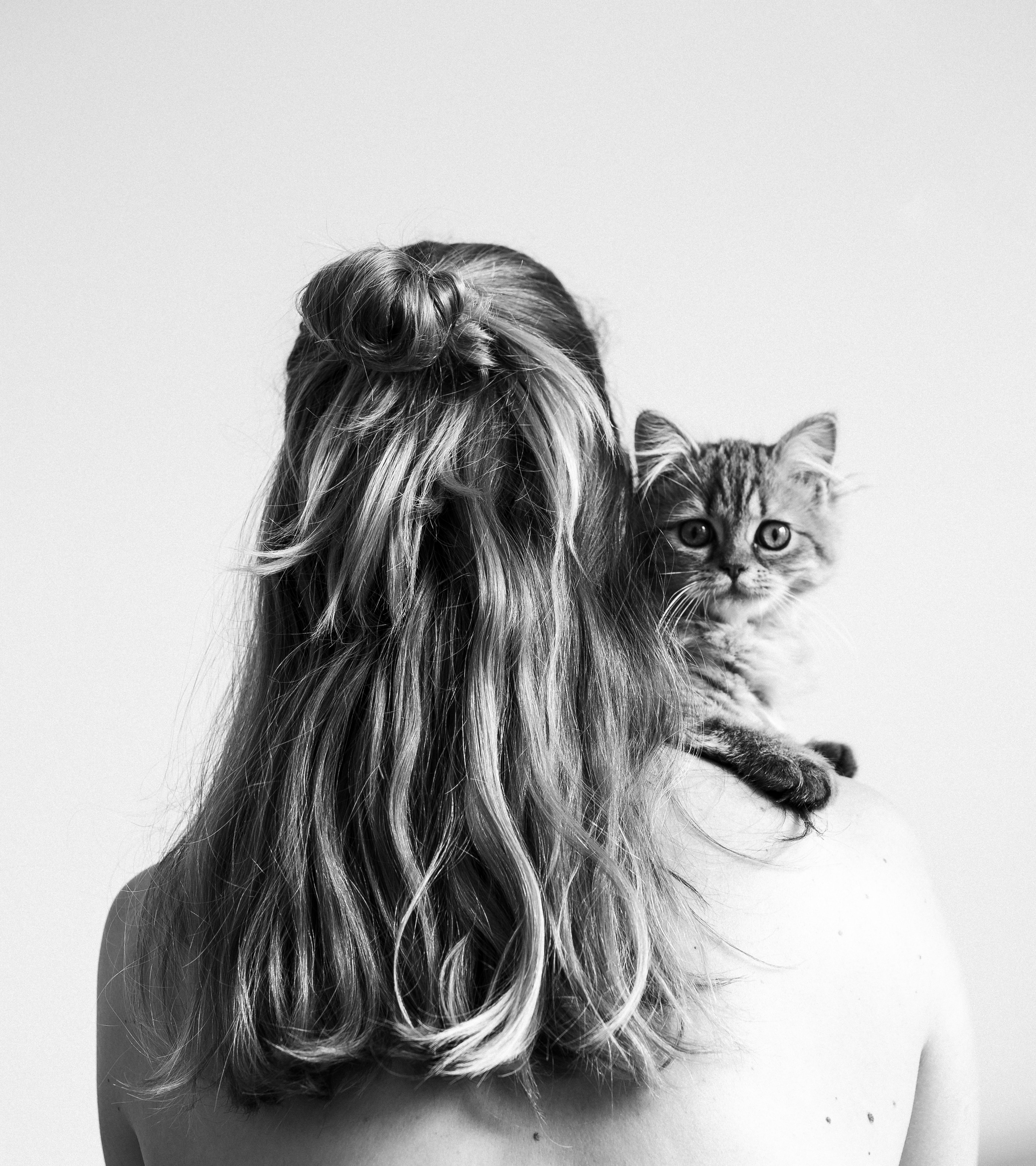 grayscale photo of woman carrying a kitten