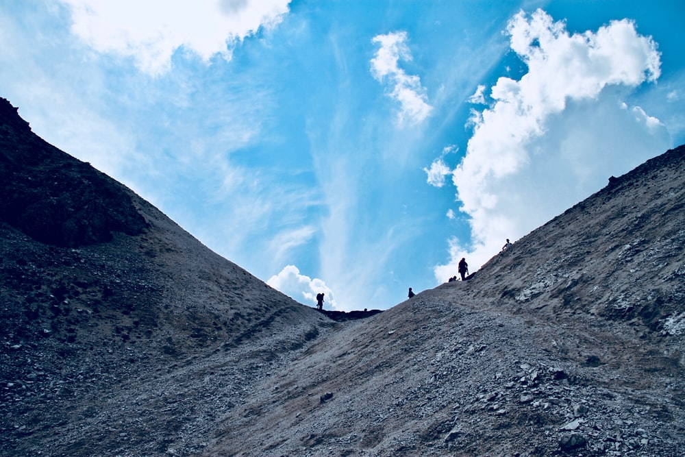 low angle photo of group of people hiking mountain