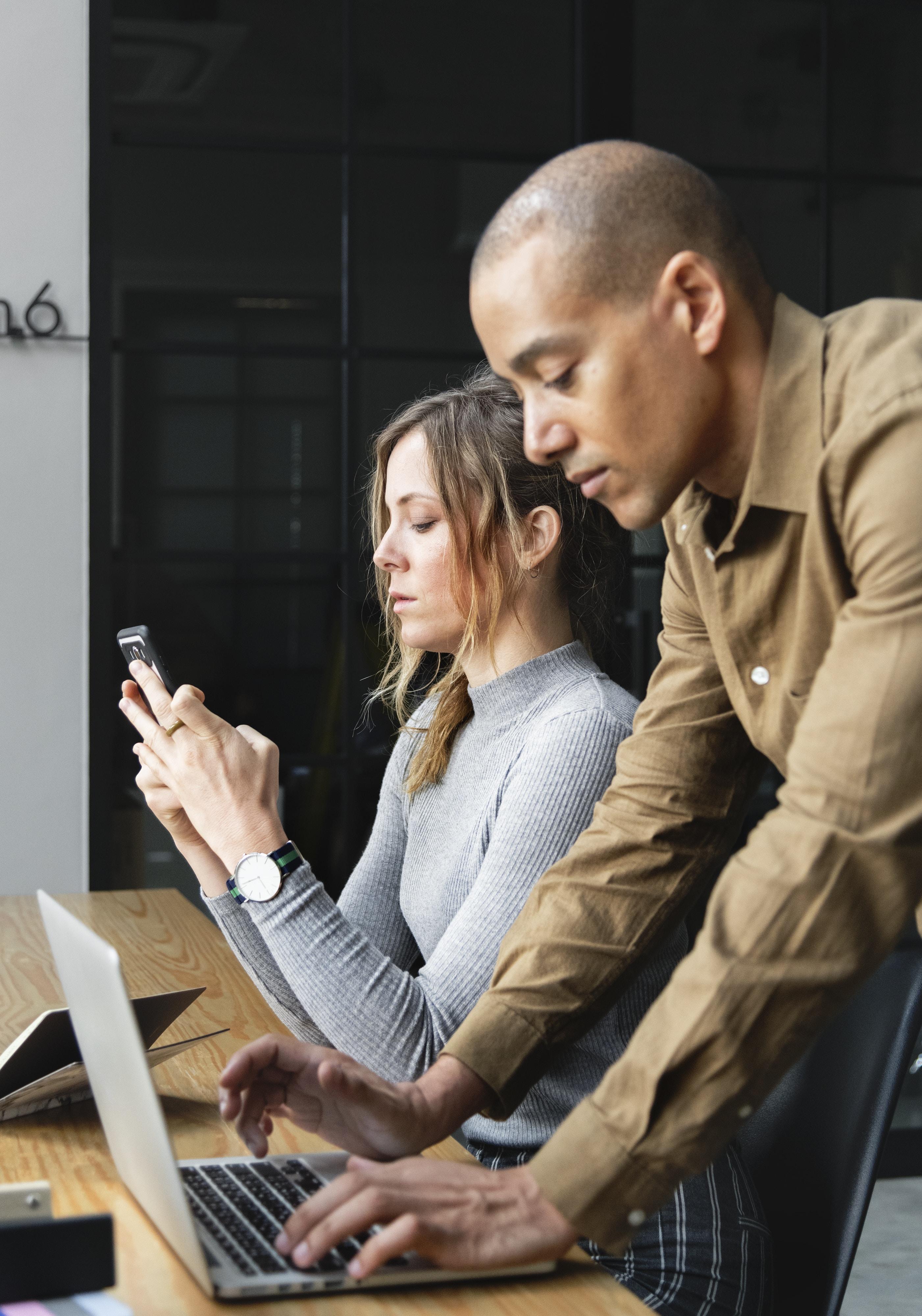 man using laptop besides woman sitting while using smartphone