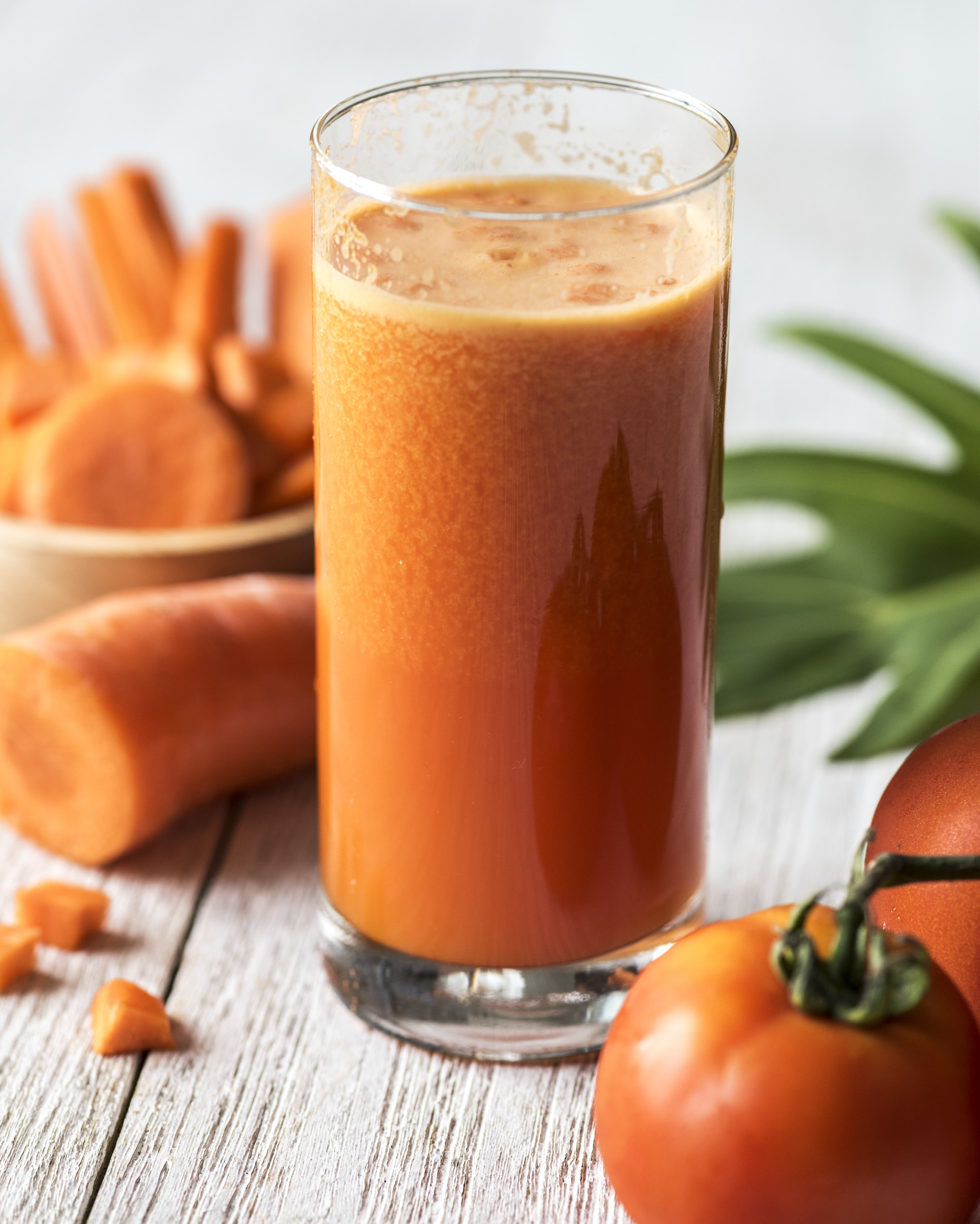 carrot juice inside clear drinking glass