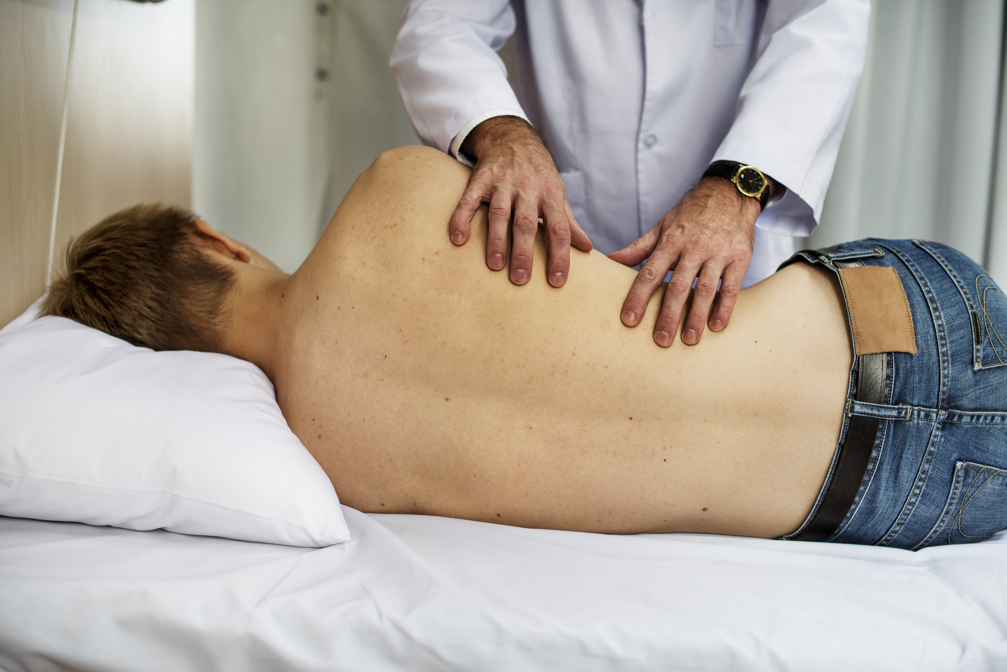 person in white long-sleeved top massaging man lying on bed inside room