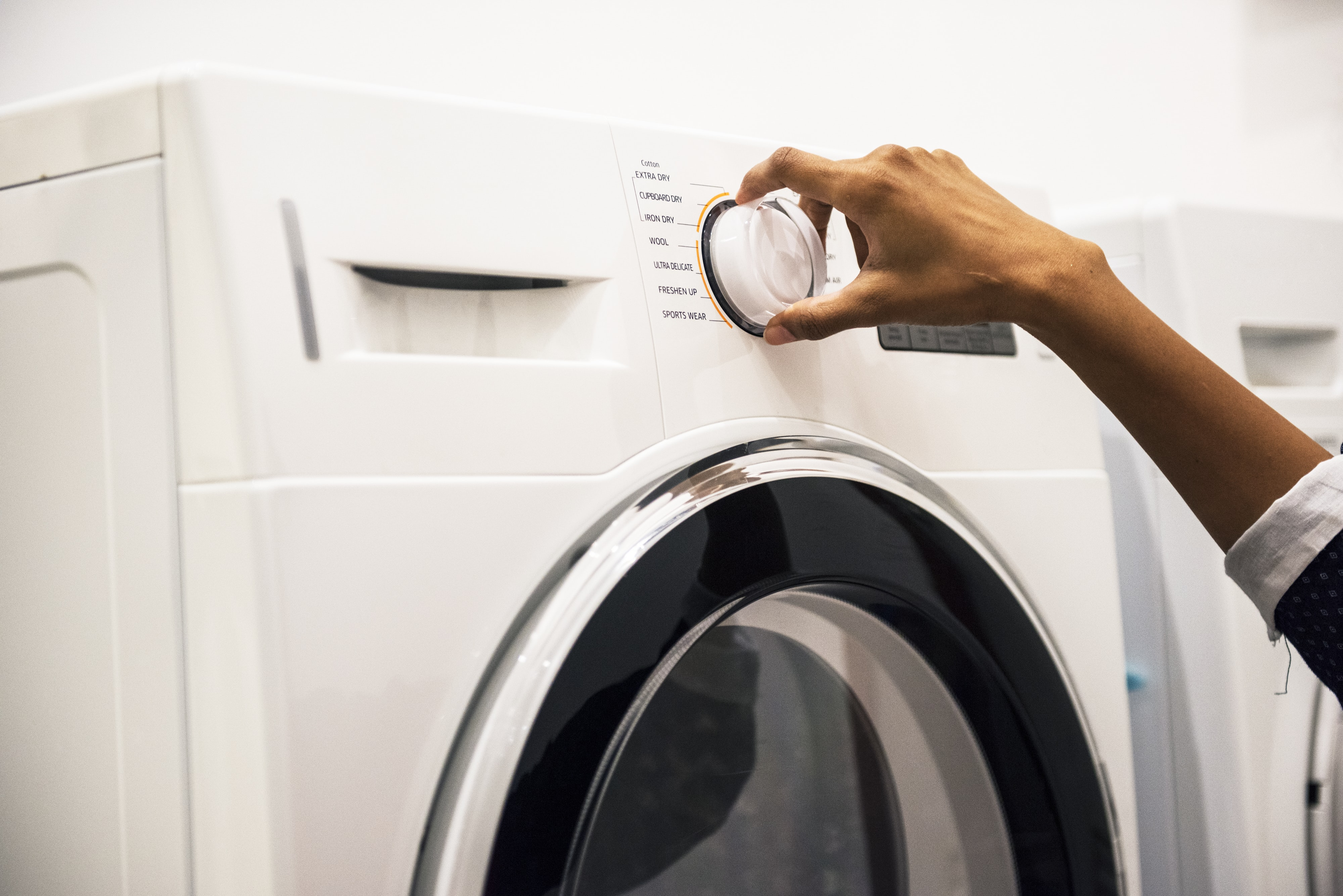 person using white front-load washing machine