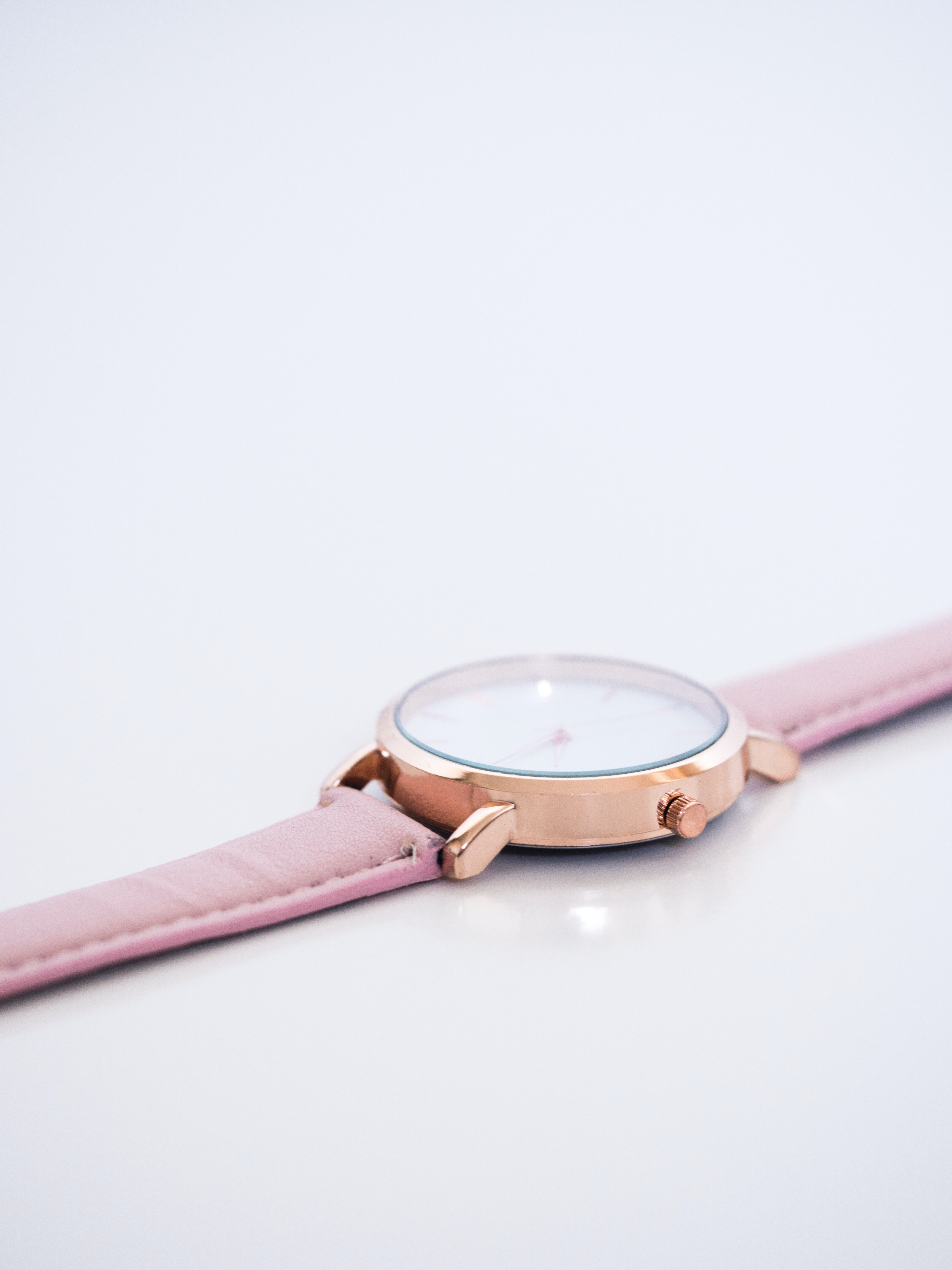round white and gold-colored analog watch on white surface