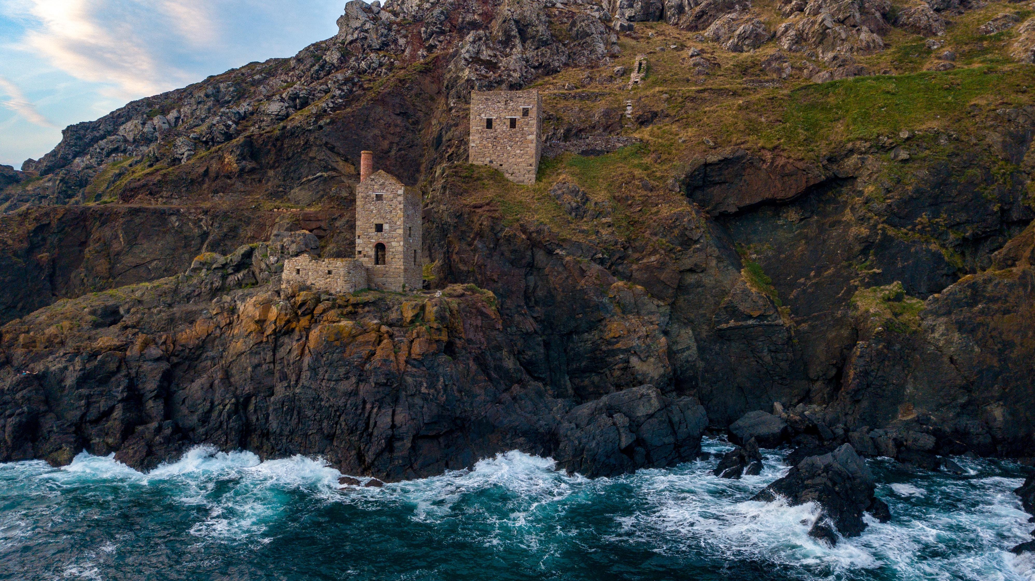 gray brick tower at cliff near ocean at daytime