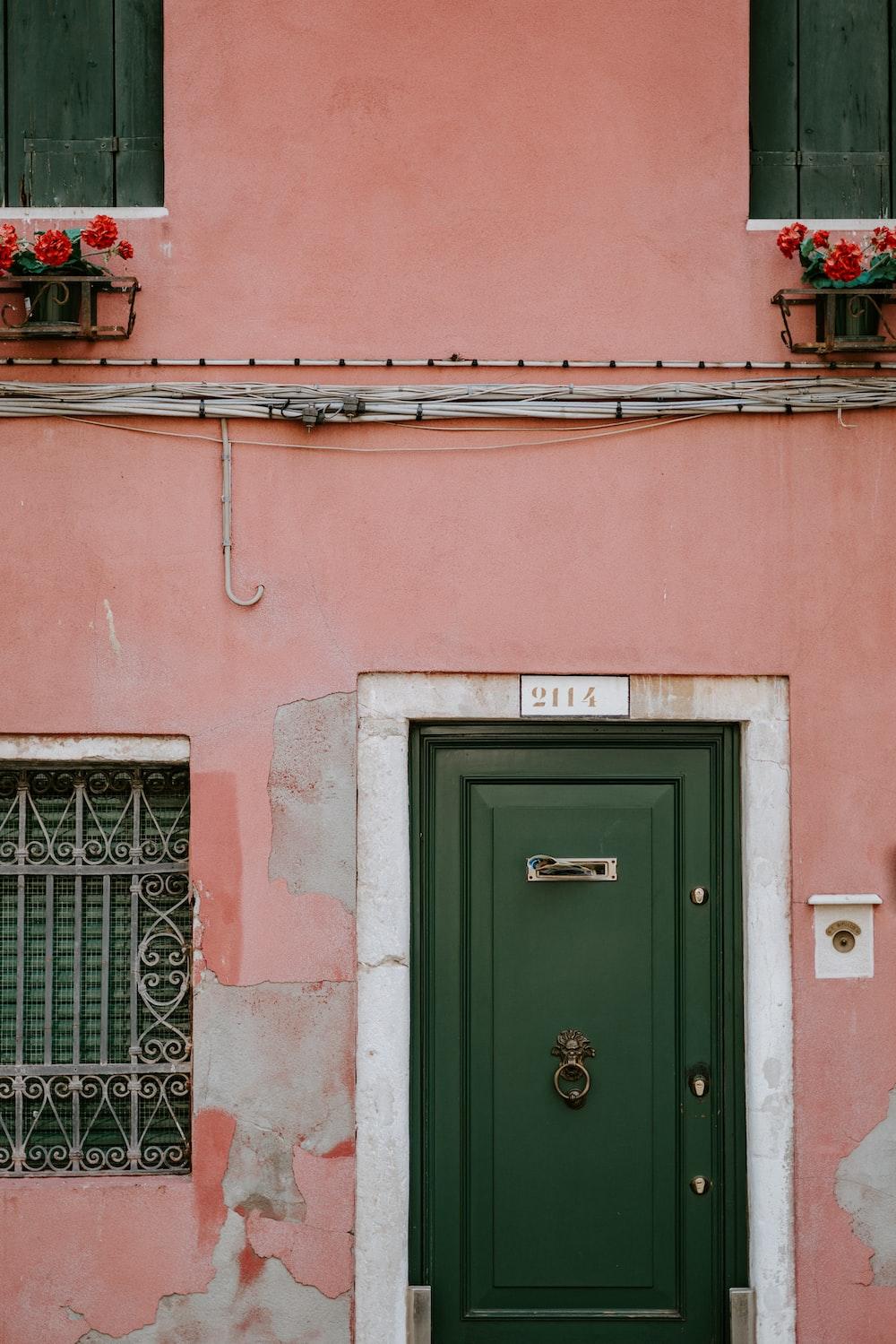 green wooden door in pink concrete building