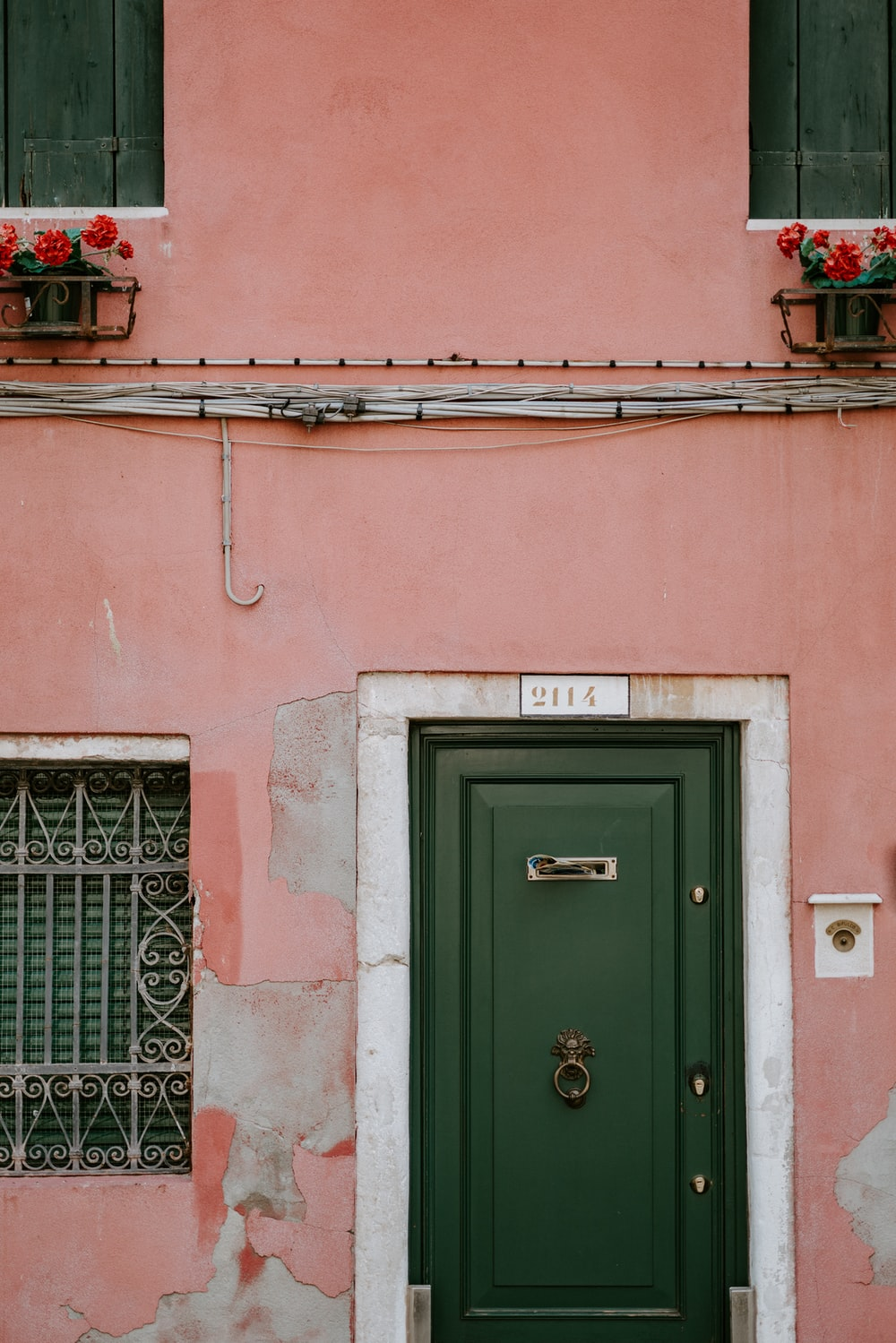green wooden door in pink concrete building
